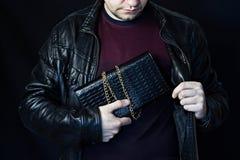 Ein Mann versteckt eine Frau ` s Handtasche in seinem Busen, der Diebstahl einer Handtasche, eine schwarze Hintergrundjacke stockbilder