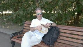 Ein Mann von mittlerem Alter in einem weißen Hemd, das auf einer Bank sitzt, studiert eine Papierkarte stock video
