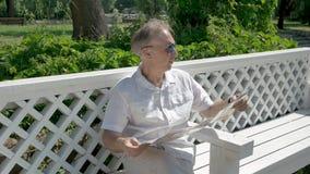 Ein Mann von mittlerem Alter in einem weißen Hemd, das auf einer Bank sitzt, studiert eine Papierkarte stock footage