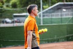 Ein Mann von mittlerem Alter spielt Tennis auf einem Gericht mit einer natürlichen Erdoberfläche an einem sonnigen Sommertag stockbild