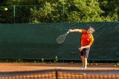 Ein Mann von mittlerem Alter spielt Tennis auf einem Gericht mit einer natürlichen Erdoberfläche an einem sonnigen Sommertag stockfoto