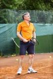 Ein Mann von mittlerem Alter spielt Tennis auf einem Gericht mit einer natürlichen Erdoberfläche an einem sonnigen Sommertag lizenzfreies stockfoto