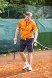Ein Mann von mittlerem Alter spielt Tennis auf einem Gericht mit einer natürlichen Erdoberfläche an einem sonnigen Sommertag lizenzfreie stockbilder