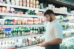 Ein Mann wählt Jogurt in einem Supermarkt Der Käufer wählt Milchprodukte vor Im System Ein Mann kauft Lebensmittel in einem Super Stockbilder
