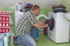 Ein Mann wäscht Kleidung in der Waschmaschine Hausarbeitmänner Mann, welche seiner Frau hilft, wenn Kleidung gewaschen wird Lizenzfreie Stockfotos