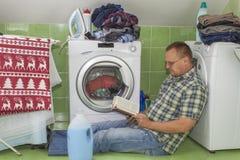 Ein Mann wäscht Kleidung in der Waschmaschine Hausarbeitmänner Mann, welche seiner Frau hilft, wenn Kleidung gewaschen wird Lizenzfreies Stockfoto