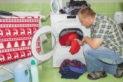 Ein Mann wäscht Kleidung in der Waschmaschine Hausarbeitmänner Mann, welche seiner Frau hilft, wenn Kleidung gewaschen wird Lizenzfreies Stockbild