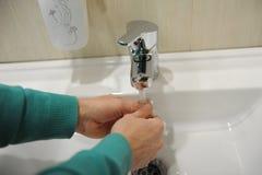 Ein Mann wäscht seine Hände über einer weißen Schüssel stockfoto