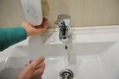 Ein Mann wäscht seine Hände über einer weißen Schüssel lizenzfreie stockfotos