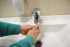 Ein Mann wäscht seine Hände über einer weißen Schüssel lizenzfreies stockbild