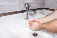 Ein Mann wäscht seine Hände im Badezimmer Stockbild