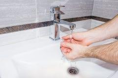 Ein Mann wäscht seine Hände im Badezimmer Lizenzfreies Stockbild