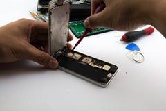 Ein Mann war Schlosser, den He zur Handyreparatur sich vorbereitet, er Änderungshandybatterie war Lizenzfreies Stockfoto