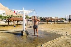Ein Mann wird unter der Dusche auf dem Strand, Totes Meer, Israel gewaschen Lizenzfreie Stockfotos