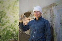 Ein Mann wirft einen Zementmörtel auf einer Backsteinmauer lizenzfreie stockfotos