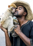 Ein Mann wirft für eine Fotografie mit seinem Affen in Djemaa EL-Fna, der Hauptplatz im Marrakesch Medina in Marokko auf Stockbilder
