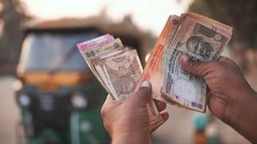 Ein Mann zählt Geld der indischen Rupie unter tuk tuk nach stock video