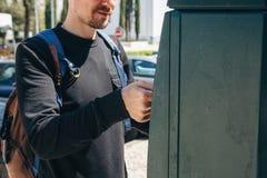 Ein Mann zahlt für das Parken unter Verwendung einer speziellen Maschine zum Lohn in Lissabon in Portugal lizenzfreie stockbilder