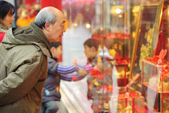 Ein Mannanschlag, zum im Fenster eines Goldsystems zu schauen Stockfotos