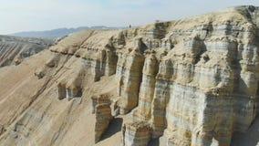 Ein Mannathlet läuft auf die Oberseite eines Hügels auf dem Gebiet der Wüstenberge Frieren Sie T?tigkeitsnahaufnahme der laufende stock video footage