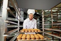 Ein Mannbäcker mit einem Behälter von kleinen Kuchen lizenzfreies stockfoto