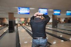 Ein Mannbowlingspiel in seinen Stuhlgängen mit seinen Händen hinter seinem Kopf Nicht ein guter Wurf von Bowlingkugeln auf dem St Lizenzfreie Stockbilder