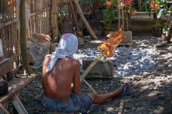 Ein Mannbraten ein ganzes Schwein auf einem Bambuspfosten über Holzkohle Lizenzfreie Stockfotos