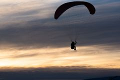 Ein Manngleitschirmfliegen hinunter einen Berg gegen einen bewölkten Sonnenuntergang im Winter lizenzfreie stockfotos