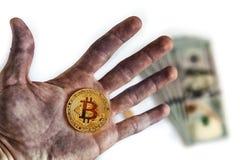 Ein Manngriff in der schmutzigen Hand eine Münze eines Schlüsselgeldes biss Münze btc bitcoin auf Hintergrunddollarbanknoten Lizenzfreies Stockfoto