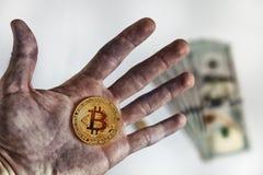 Ein Manngriff in der schmutzigen Hand eine Münze eines Schlüsselgeldes biss Münze btc bitcoin auf Hintergrunddollarbanknoten Lizenzfreie Stockfotos