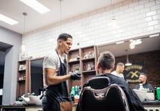 Ein Mannkunde, der mit haidresser und Herrenfriseur im Friseursalon spricht lizenzfreies stockfoto