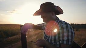 Ein Mannlandwirt trägt einen Hut bei Sonnenuntergang und arbeitet an einem smarphone Kommunikation mit Kunden Modernes Geschäft stock video