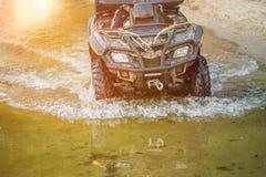 Ein Mannreitengeländewagen u. ein x28; ATV& x29; geht entlang sandige Küste des Sees oder des Flusses, spritzt die Herstellung un stockfotos
