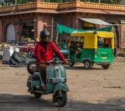 Ein Mannreitenvespa auf Straße lizenzfreie stockbilder