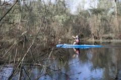 Ein Mannrudersport im Kanu auf einem ruhigen Fluss, dessen Banken umfaßtes w sind Stockfotografie