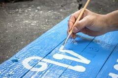 Ein Mannschreiben unterzeichnet Brett mit einer Bürste von Aquarellen auf Zementbodenhintergrund Malerei auf hölzernem Brett in d lizenzfreie stockfotografie