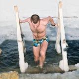 Ein Manntauchen im Eisloch auf dem See im Winter Stockfotografie