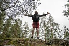Ein Manntourist mit einem Rucksack steht auf einem Felshügel in einem Kiefernwald, die ausgestreckten Arme Konzept der Freiheit lizenzfreie stockfotos