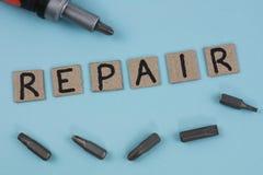 Ein manueller Schraubenzieher und fünf Bits für Schraubenzieher nahe handgeschriebenem Wort REPARATUR auf Pappquadraten lizenzfreie stockbilder