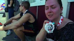 Ein Marathonteilnehmer, ein junges Mädchen, nachdem er gelaufen ist, sitzt im Schatten, Reste, Aktien ihre Eindrücke, Getränkwass stock footage