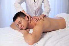 Ein Massagetherapeut lässt einen Mann Badekurgesundheit massieren stockfotos