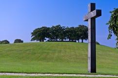 Ein massives frommes Kreuz auf einem blauen Himmel Stockfotos