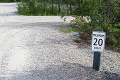 Ein Maximum 20 Kilometer pro Stundenzeichen entlang einer Schotterstraße Lizenzfreie Stockfotos