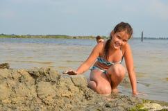 Ein Mädchen, das mit Sand an der Küste spielt Stockfotos