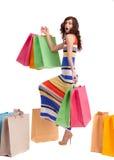 Ein Mädchen in einer langen Kleidfarbe mit Einkaufenbeuteln Lizenzfreies Stockbild