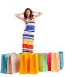 Ein Mädchen in einer langen Kleidfarbe mit Einkaufenbeuteln Stockbilder
