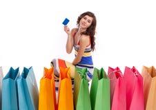 Ein Mädchen in einer langen Kleidfarbe mit Einkaufenbeuteln Lizenzfreie Stockfotos