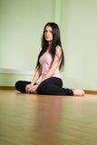 Ein Mädchen mit dem langen schwarzen Haar, das auf dem Fußboden sitzt Lizenzfreies Stockbild