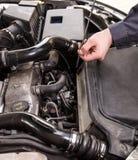 Ein Mechaniker überprüft das Öl auf Auto Stockfotos
