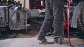 Ein Mechaniker und Arbeitskräfte reparieren einen LKW an der Station stock footage